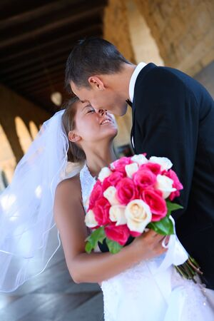 asian bride: A beautiful woman bride and handsome man groom kissing at church during wedding Stock Photo