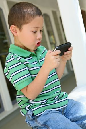 A young boy playing video game on porch at home photo