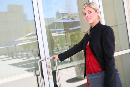 A pretty blonde business woman entering her company