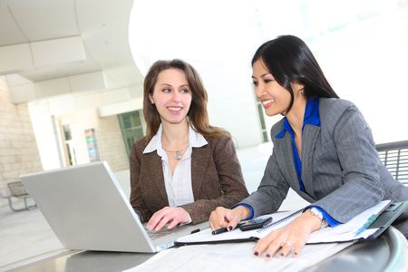 A diverse business woman team at office building on laptop computer