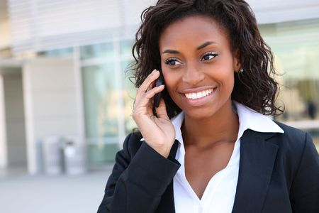 attractive person: Pretty african americanl business woman talking on her mobile phone at office building  Stock Photo