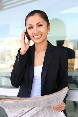 A pretty asian business woman on the phone at office building photo