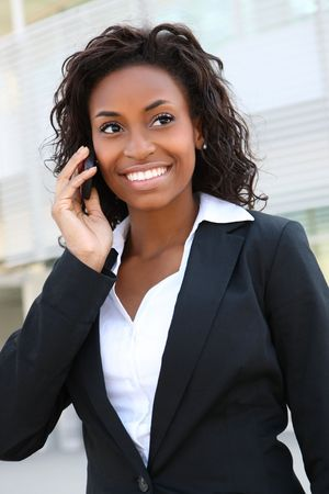 phone business: Pretty african americanl business woman talking on her mobile phone at office building  Stock Photo