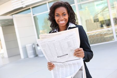 Pretty african american business woman reading newspaper at office building  photo