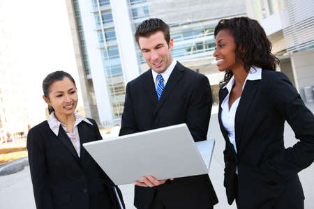 A diverse attractive man and woman business team at office building with laptop computer photo
