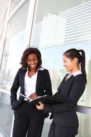 Two interracial (african and asian) business women team at office building photo