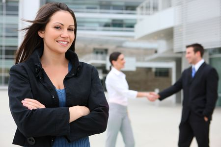 company building: A pretty business woman with team handshake in background Stock Photo