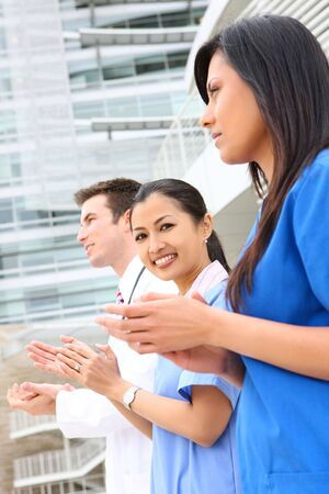 medical doctors: A successful man and woman medical team outside hospital clapping