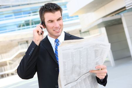A young, handsome business man at the office building on phone with newspaper photo
