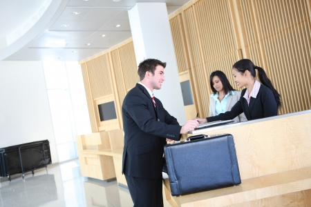 checking in: A handsome business man checking in with pretty women in company lobby