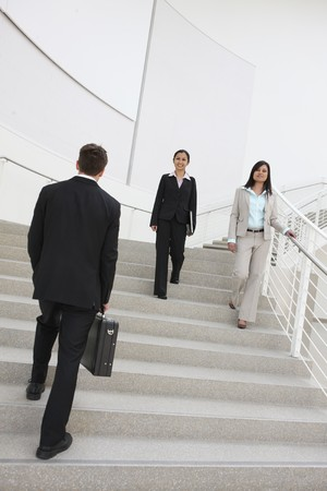 Diverse man and woman workers at the office building on stairs photo