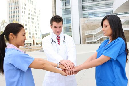 A successful man and woman medical team outside hospital clapping