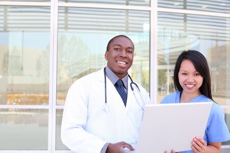 An ethnic medical man and woman team outside hospital on laptop computer photo