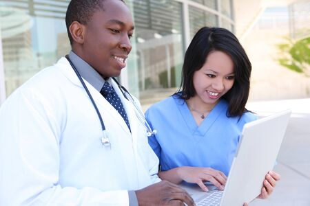An ethnic medical man and woman team outside hospital on laptop computer Stock Photo - 7011049