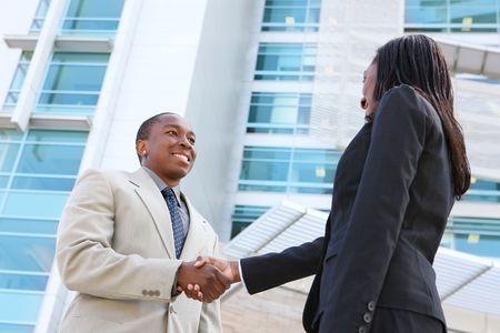 Een Afrikaanse Amerikaanse zaken man en vrouw team handshake op kantoor gebouw