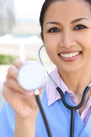 general practitioner: A pretty asian woman nurse outside  hospital building Stock Photo