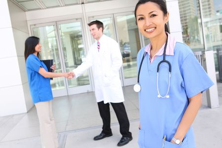 A successful man and woman medical team outside hospital  photo
