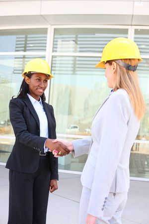 An attractive woman architect team on construction site handshake photo