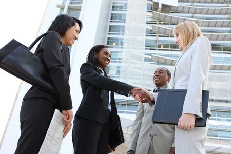 A diverse business man and woman team handshake at office building photo