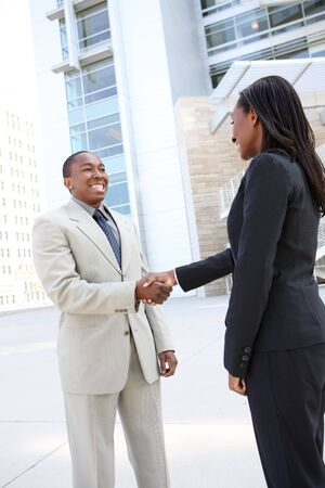 african american handshake: An african american business man and woman team handshake at office building Stock Photo
