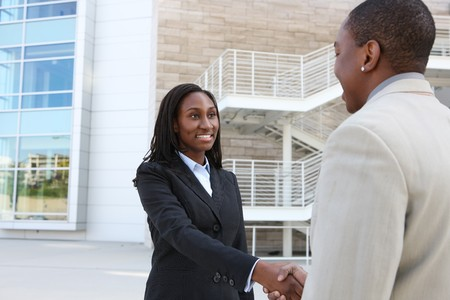 An african american business man and woman team handshake at office building photo