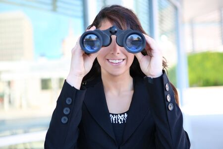 Young caucasian business woman looking through binoculars at office building Stock Photo - 7118302