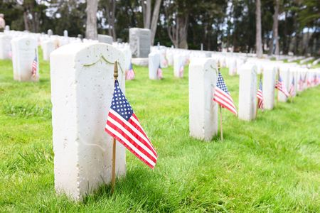 American flags on tombstones in cemetery at memorial day remembrance photo