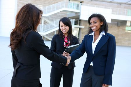 A pretty diverse young business woman team at office building handshake Stock Photo - 7118305