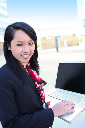 A young pretty asian business woman on laptop computer at office photo