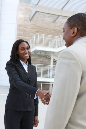 An african american business man and woman team handshake at office building Stock Photo