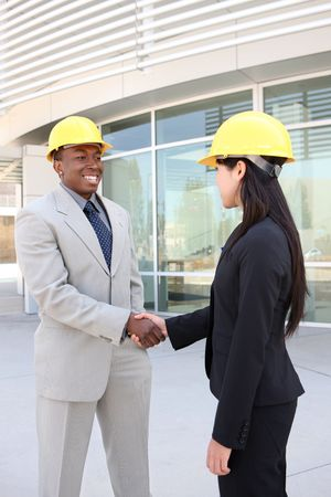 An attractive man and woman architect team on construction site handshake photo