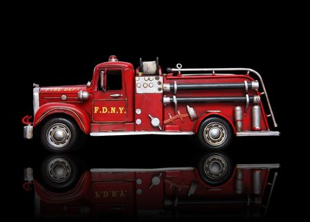 engine fire: An old vintage fire truck isolated over black Stock Photo