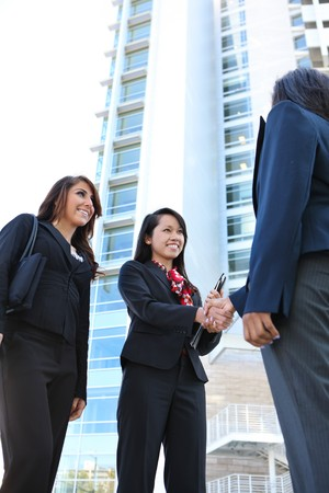 A pretty diverse young business woman team at office building handshake Stock Photo - 7346030