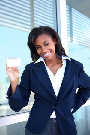 african business: African American woman holding business card at office building