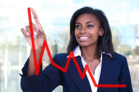 Pretty business woman drawing a graph on a glass window at office - focus is on woman  Stock Photo - 7248498