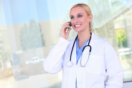 A young pretty woman nurse at hospital on cell phone