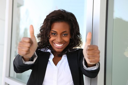 corporation: A pretty african american business woman with thumbs up  Stock Photo