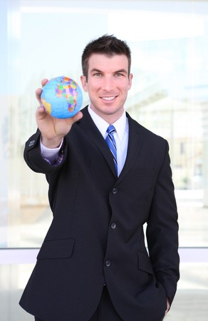 A handsome young business man holding a globe at office building photo