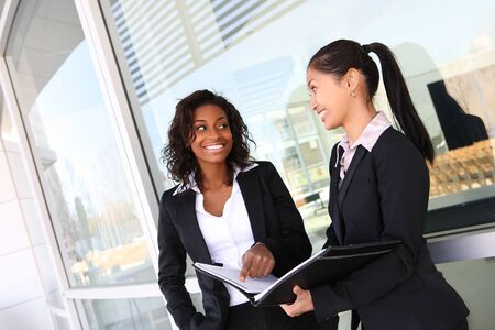 Two ethnic asian and african business women team at office building photo