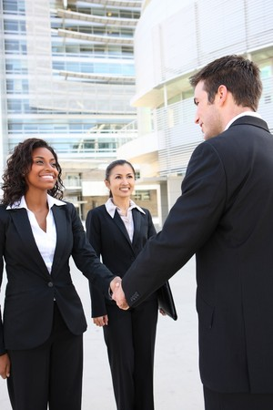 A diverse attractive man and woman business team handshake at office building Фото со стока