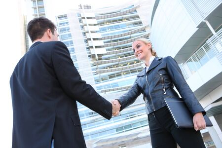 Pretty blonde caucasian business woman shaking hands with a man in her office