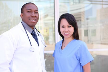 An ethnic happy medical man and woman team outside hospital photo