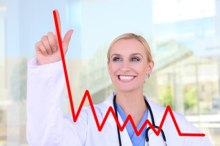 practise: A pretty young nurse at hospital drawing a growth graph