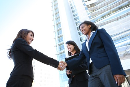 business woman: A pretty diverse young business woman team at office building handshake Stock Photo