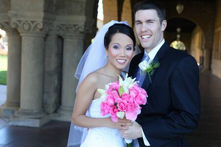 religious event: A beautiful bride and handsome groom at church during wedding Stock Photo