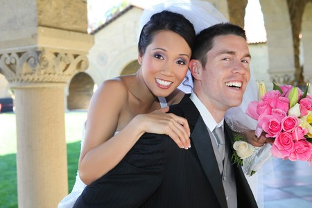 interracial marriage: A beautiful bride and handsome groom at church during wedding Stock Photo