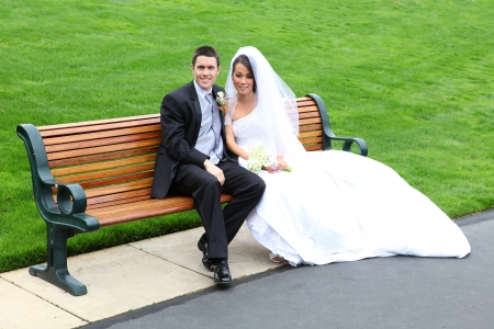 A beautiful bride and handsome groom on grass during wedding photo