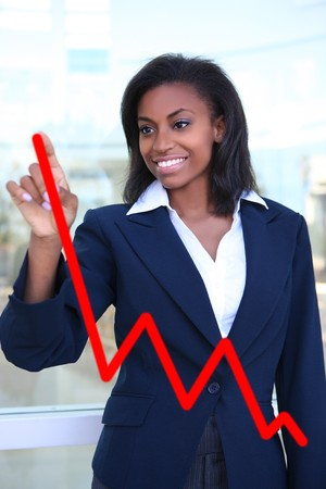 Pretty business woman drawing a graph on a glass window at office - focus is on woman  photo