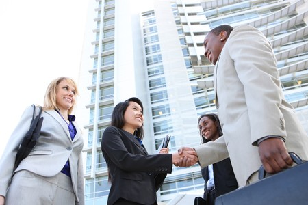 A diverse attractive man and woman business team handshake at office building photo