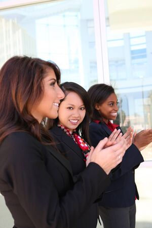 A diverse attractive woman business team at office building clapping photo
